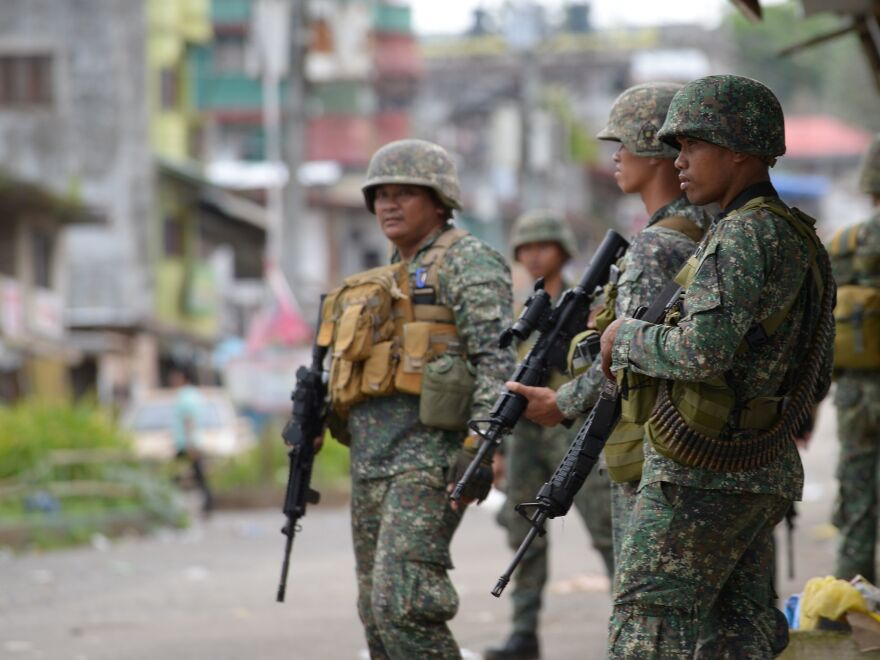 Philippine troops stand guard near the town center in Marawi on Sunday.