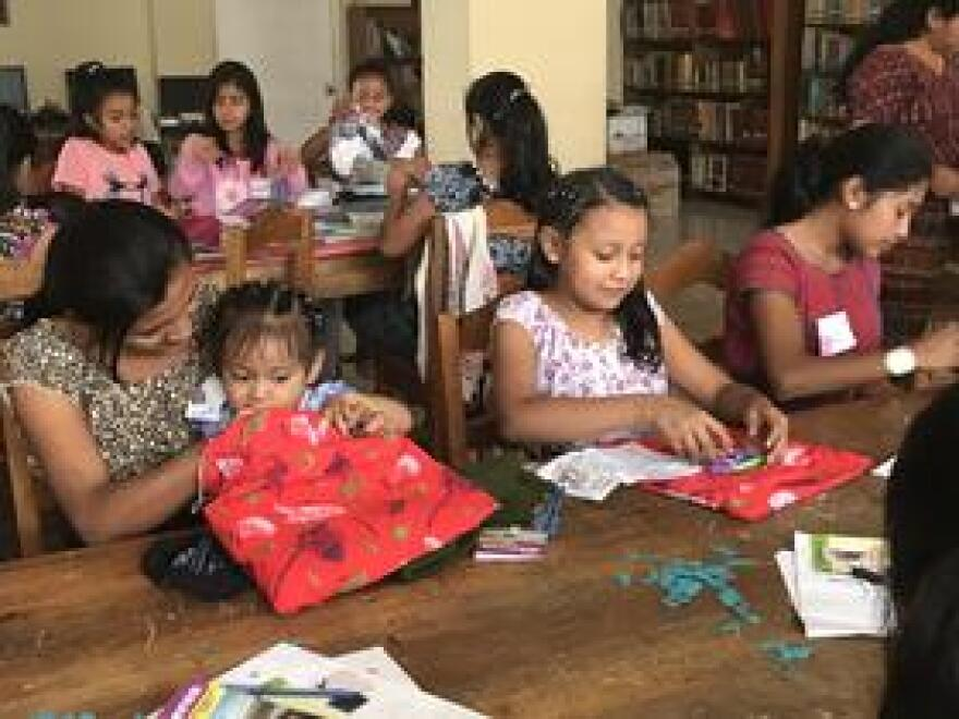 The women of varying ages in San Juan la Laguna learning how to use the reusable menstrual pads, and fertility bracelets made and brought by women of Fort Myers.