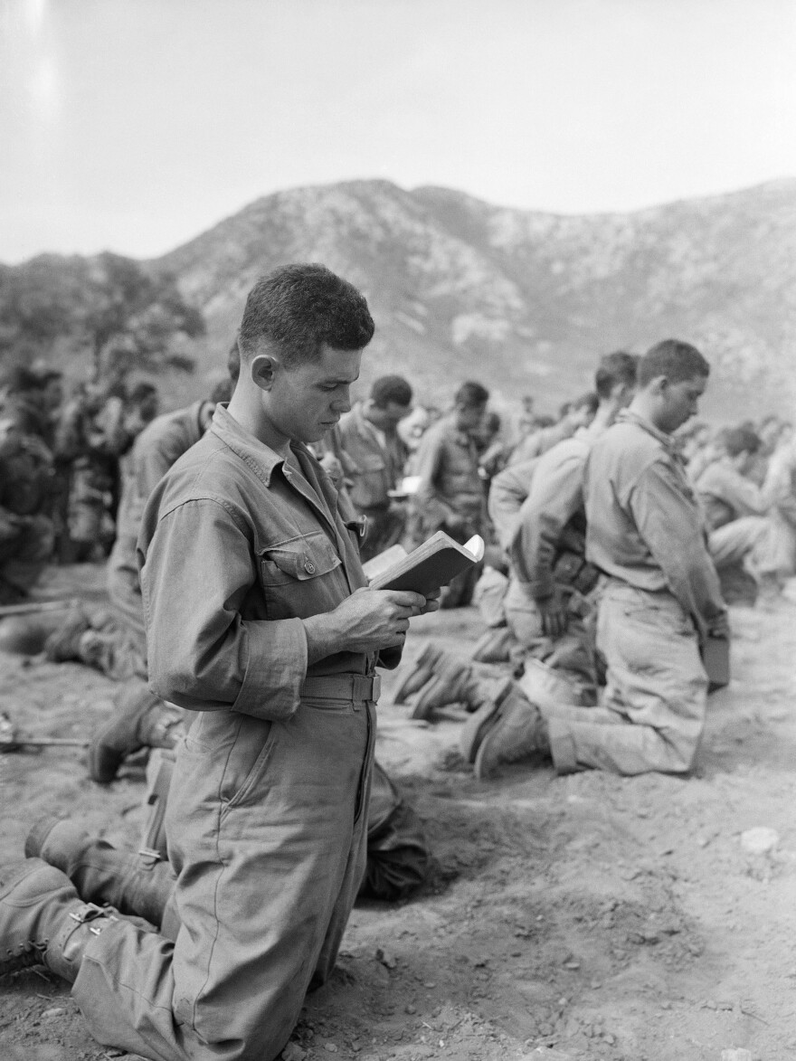 Sgt. Eric Cestero kneels with other members of the 65th Infantry Regiment during a memorial Mass in honor of Borinqueneers killed in battle in Korea in 1951.