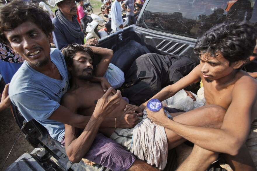 A sick migrant is helped by friends to board a truck that is taking them to a local hospital upon arrival in Simpang Tiga, Indonesia on Wednesday.