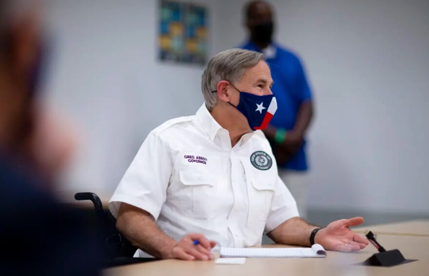Gov. Greg Abbott wears a face mask at a press conference.