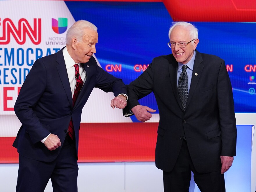 Joe Biden and Bernie Sanders touch elbows, as they greet each other for a Democratic presidential debate last month.