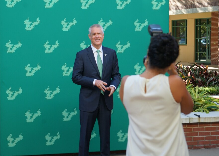 USF President Steven Currall poses for a photo in front of a backdrop.