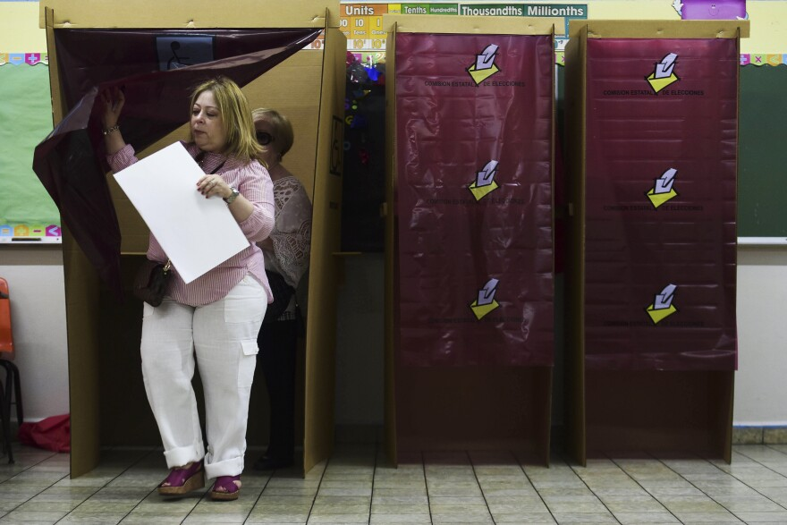 A woman exits the voting booth in San Juan during Puerto Rico's nonbinding referendum Sunday. Puerto Rican voters are weighing whether to ask Congress for statehood.