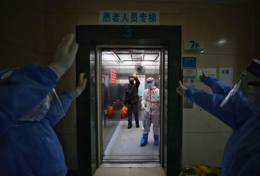 Medical staff wave goodbye to a recovered COVID-19 coronavirus patient at the Red Cross Hospital in Wuhan in China's central Hubei province on March 16, 2020. (STR/AFP via Getty Images)