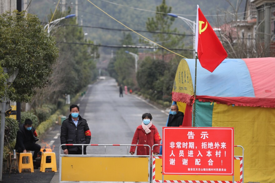 Volunteers guard a visitor checkpoint at the entrance to a village in Hangzhou in east China's Zhejiang province on Feb. 3. The notice warns that outsiders aren't allowed into the village.