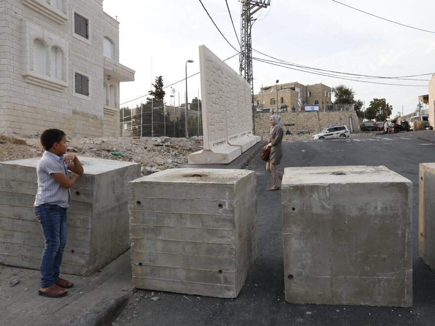 Palestinians look at a new concrete wall erected by Israeli security forces in the East Jerusalem neighborhood of Jabel Mukaber.