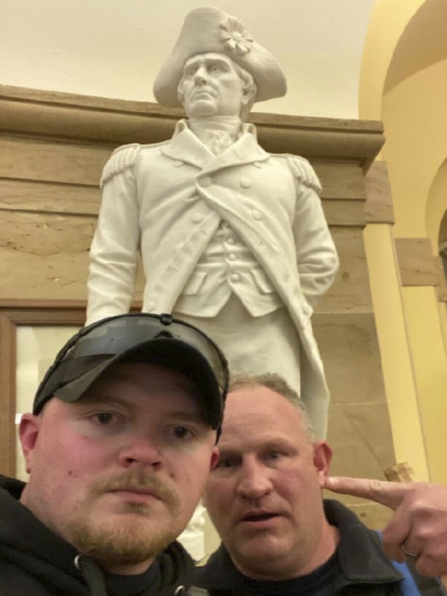 "This photo, which was made available by the United States Capitol Police in a complaint and arrest warrant, shows Rocky Mount Police Department Sgt. Thomas ""T.J."" Robertson and officer Jacob Fracker in the Capitol. Both Robertson and Fracker are also U.S. military veterans."