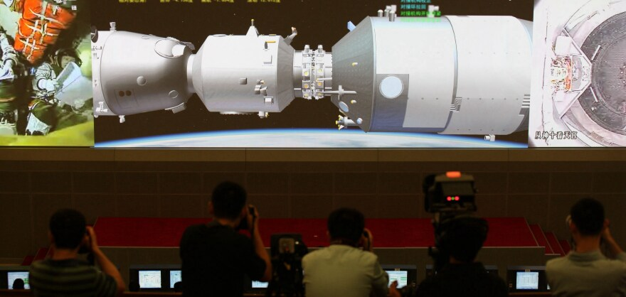 Scientists look at the screen showing the Shenzhou X manned spacecraft docking with the orbiting Tiangong-1 space module at Beijing Aerospace Control Center on June 13, 2013, in Beijing.