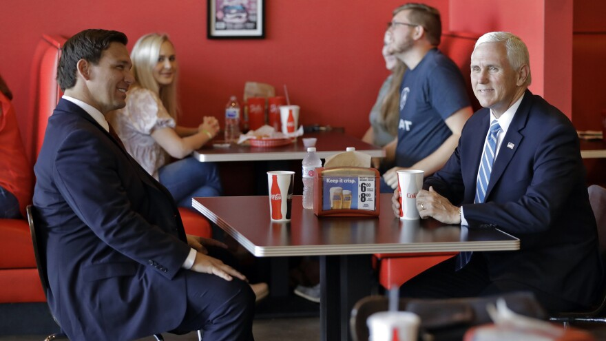 Vice President Mike Pence, right, talks to Florida Gov. Ron DeSantis as they wait for their lunch at Beth's Burger Bar, Wednesday, May 20, 2020, in Orlando, Fla.