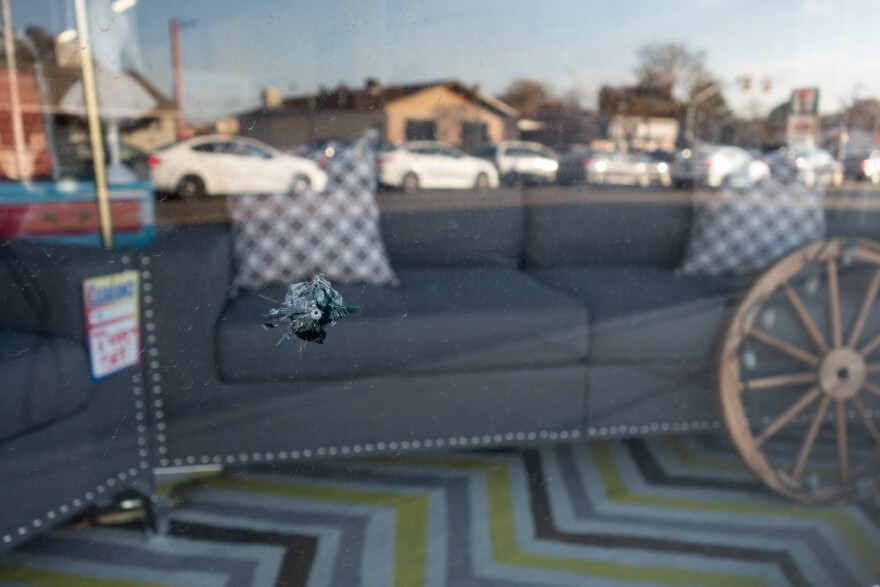 A bullet hole is visible in a display window looking into a furniture store.