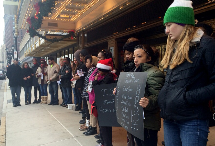 Demonstrators calling for justice for Eric Garner and Michael Brown held a moment of silence outside the Fox Theatre on Sunday, December 7, 2014.