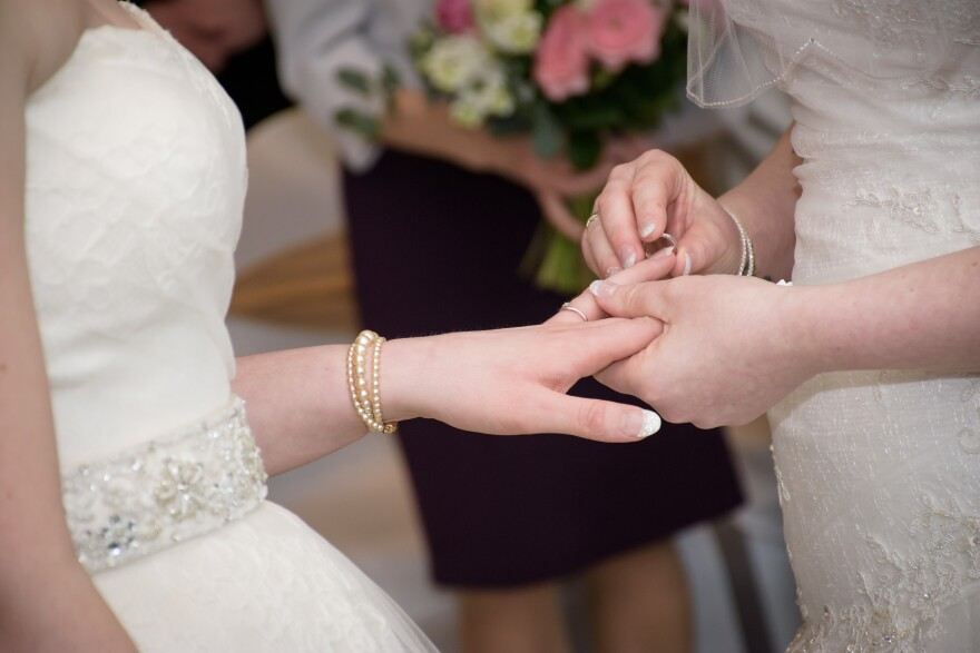 close-up of one hand putting a ring on another person's hand