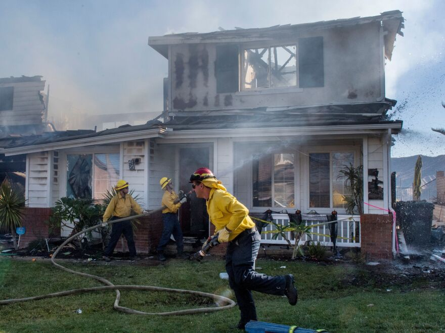 Firefighters hose down a burning house during the Tick Fire in Agua Dulce, near Santa Clarita, Calif., on Friday.