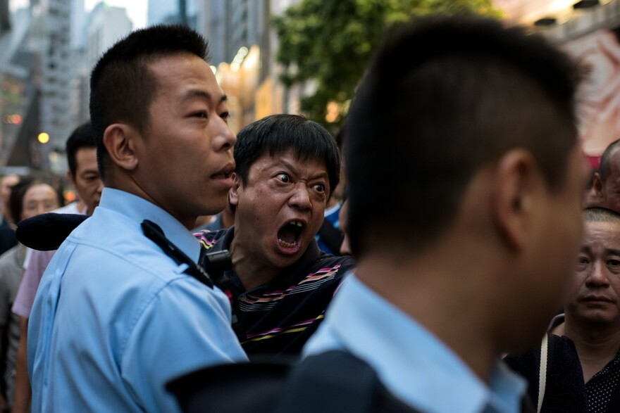 A man is held back by police as he screams at pro-democracy protesters to stop occupying an area of the Causeway Bay district.