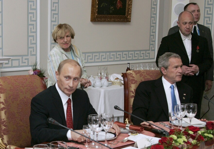 "In a 2006 photo, Russian President Vladimir Putin (left) hosts U.S. President George W. Bush in St. Petersburg, Russia. At second right is Russian businessman Yevgeny Prigozhin, known as ""Putin's chef."" The U.S. has charged Prigozhin with running an Internet operation that interfered with the 2016 U.S. presidential election. He's also been sanctioned for supporting Russia's occupation in Ukraine."