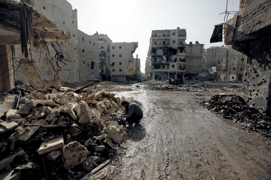 A man is seen in the al-Amirya neighborhood of the city of Aleppo on Sunday. Syrian artillery and aircraft also battered rebel positions in and around Damascus in an operation to secure the capital.