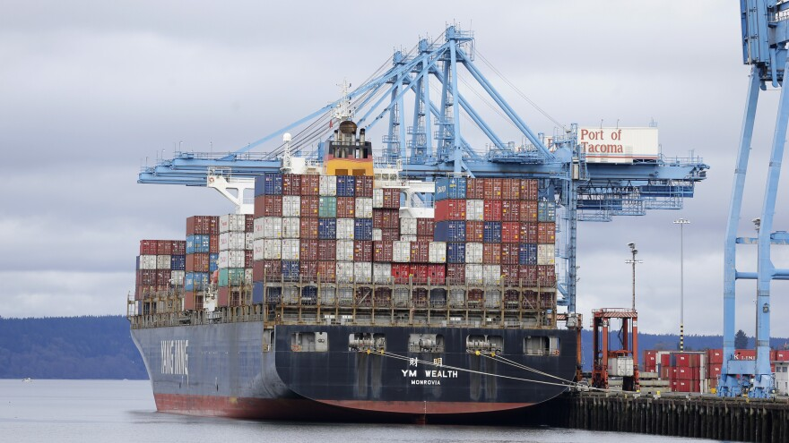 A cargo container ship operated by Yang Ming Marine Transport Corp. sits docked Friday at the Port of Tacoma. Negotiators for the two sides in the labor dispute that has snarled international trade at U.S. West Coast seaports reached a settlement late Friday.