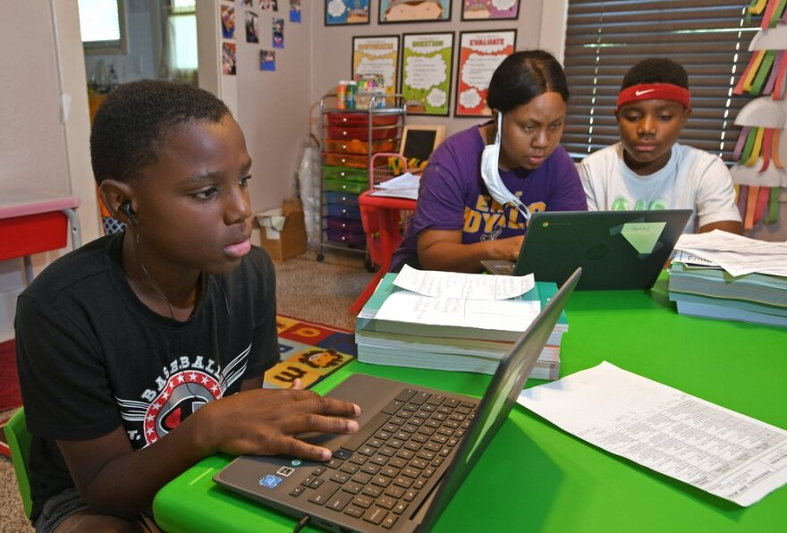 Two boys work on laptops as their mother helps.