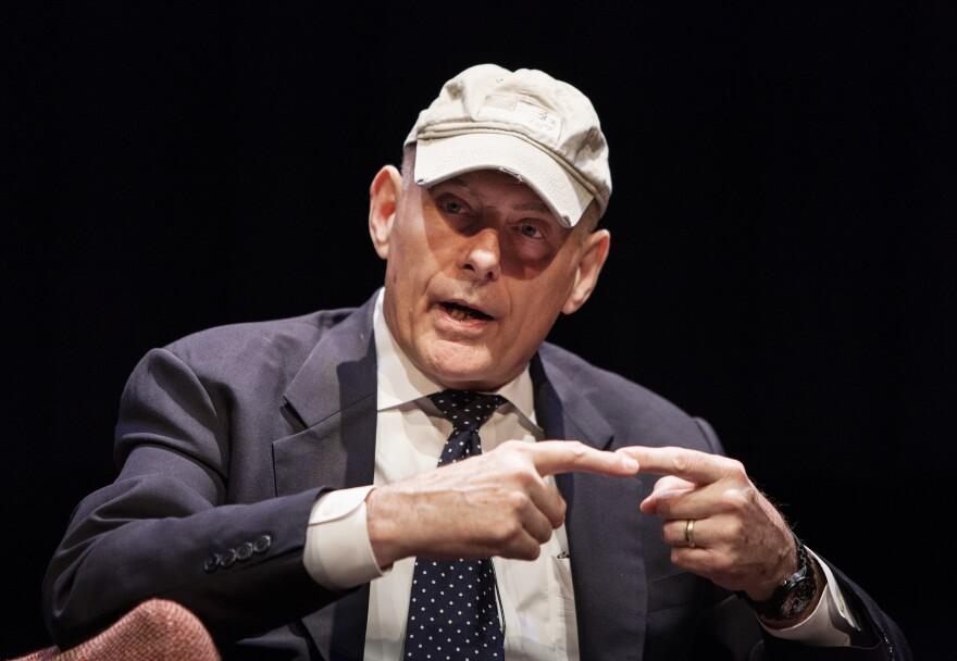 Close-up photo of man wearing hat, speaking.