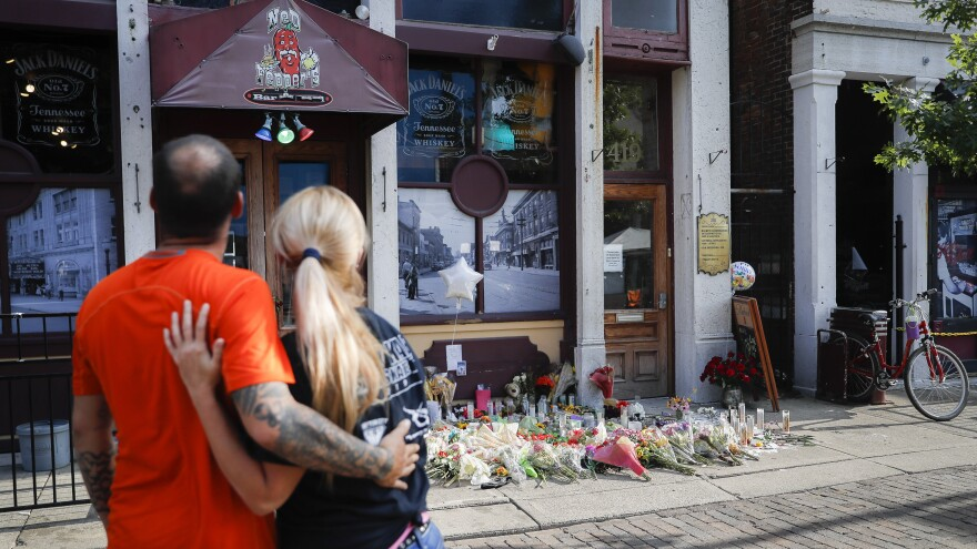 Mourners view flowers and other mementos left in honor of the people killed or injured during Sunday's mass shooting outside Ned Peppers bar in the Oregon District of Dayton, Ohio.