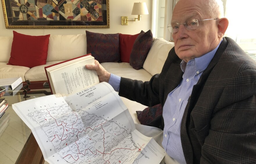 Attorney Emmet Bondurant holds a map of Georgia's congressional districts around the early 1960s, exhibit #9 in the <em>Wesberry v. Sanders </em>case he argued before the Supreme Court as a young lawyer.