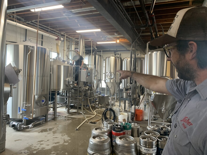 Man pointing at beer brewing equipment.