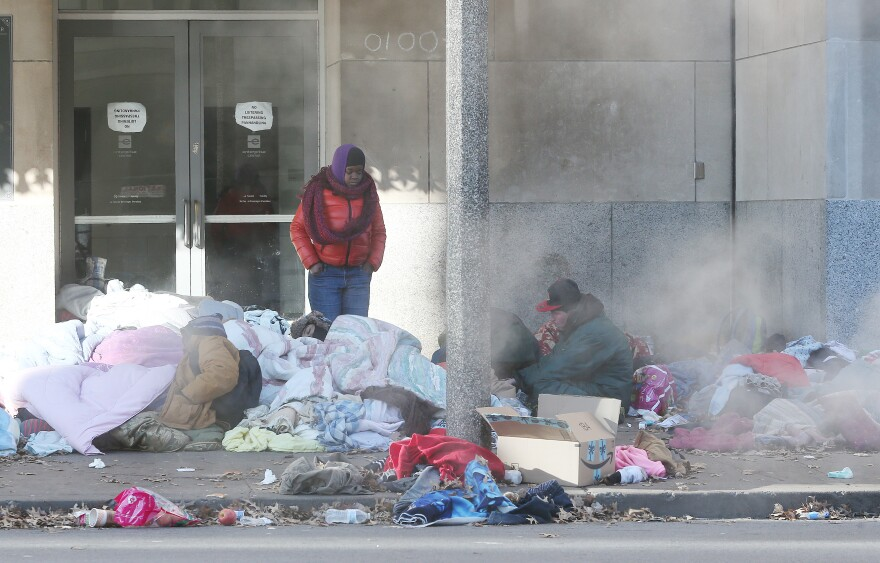 Homeless people huddle over steam grates near the Enterprise Center in January 2019.