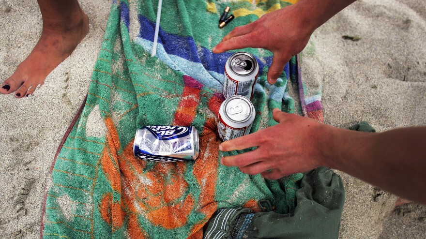 A college student reaches for a beer during spring break in Miami.