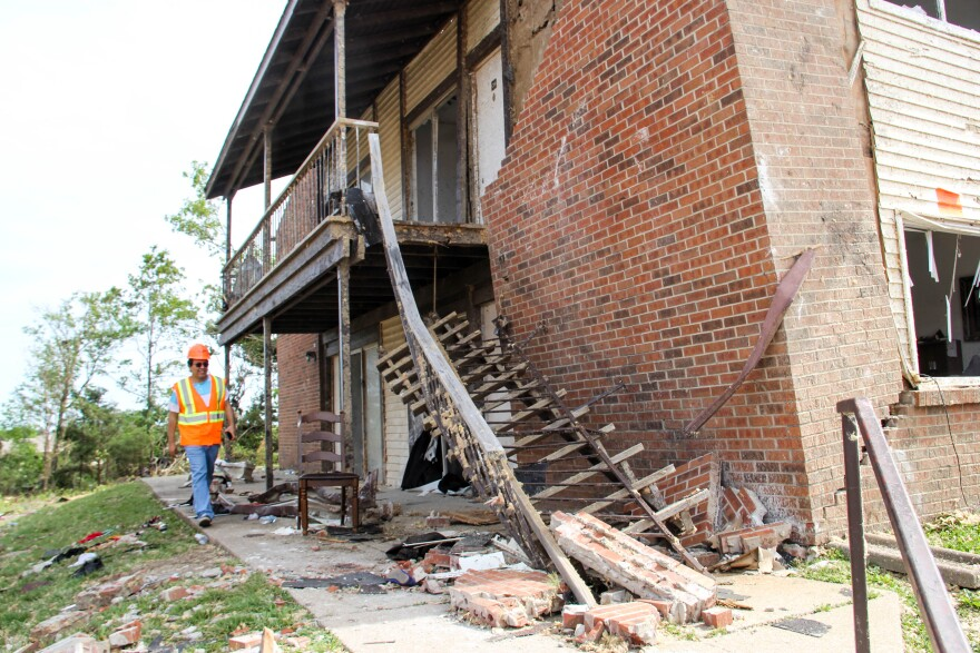 Missouri S&T engineering professor Mohamed ElGawady walks by a building where a building's staircase and brick veneer had collapsed.