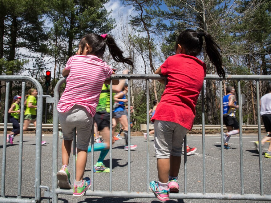 "Children climb the barrier to watch the Boston Marathon runners in the iconic ""scream tunnel"" near Wellesley College on April 17, 2017, in Wellesley, Ma."