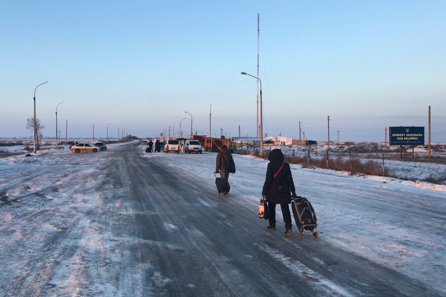 People cross from Russian-controlled Crimea to the Ukrainian mainland at a border post outside the town of Chonhar in January 2015.