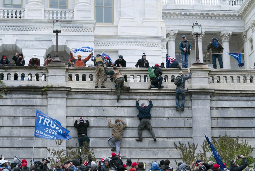 Rioters climb the west wall of the the U.S. Capitol.