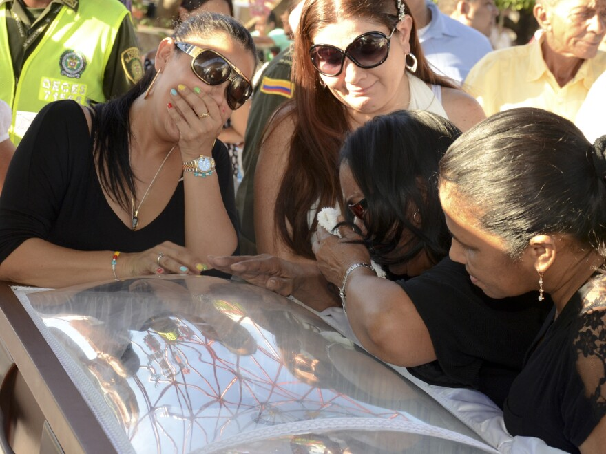 Diomedes Diaz's widow, Luz Consuelo Martinez (top left), mourns over the performer's coffin after he died of a heart attack in 2013. Diaz had been convicted of killing a girlfriend in 1997, but he served only two years in prison and then made a spectacular comeback.