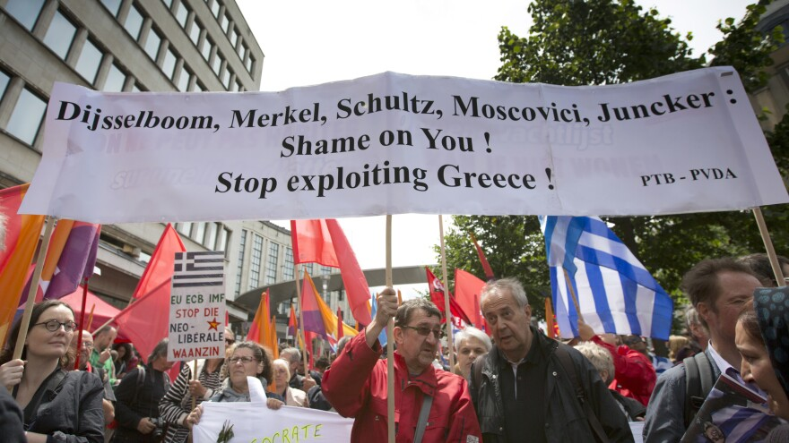Demonstrators hold flags and banners during a protest march in solidarity with Greece in Brussels on Sunday. Heads of state in the eurozone will meet in Brussels on Monday for a special summit to discuss the financial crisis with Greece.