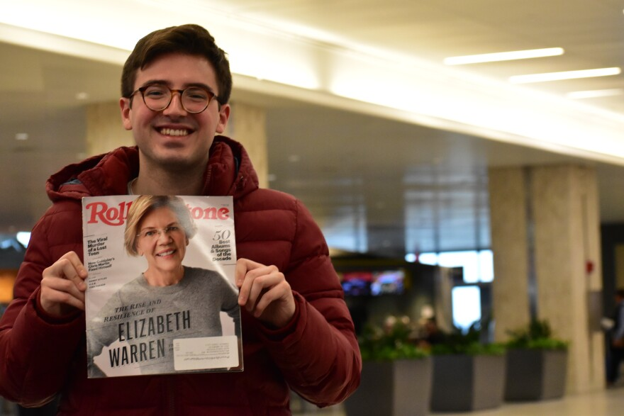 Student standing in an airport smiles with a copy of Rolling Stone. Candidate Elizabeth Warren is on the cover