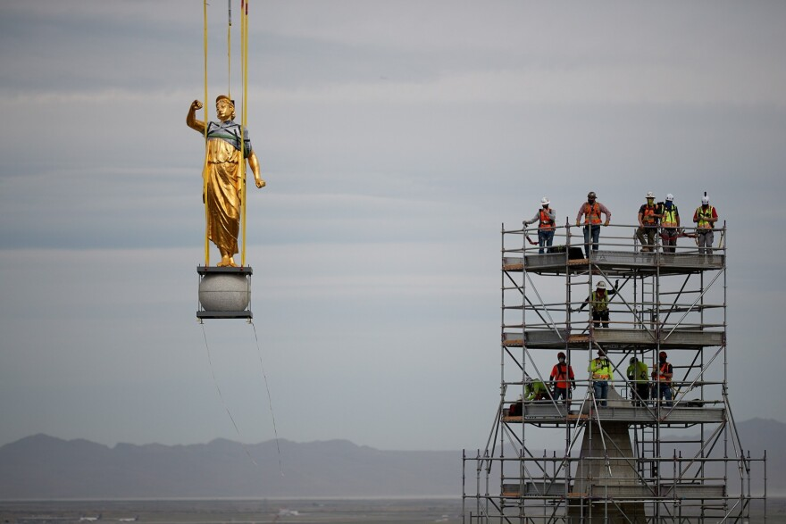 Photo of the statue hanging from a crane after being removed from the building