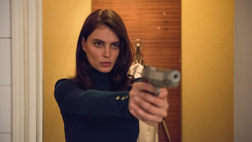 Gilda (Catrinel Marlon) threatens to send bullets whistling through the air in <em>The Whistlers</em>.