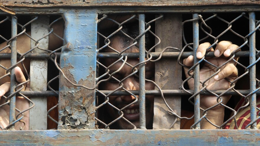 A Bangladeshi border guard cries inside a prison van as he leaves a special court after a verdict in Dhaka, Bangladesh, on Tuesday. The court sentenced 152 people to death for a 2009 mutiny by disgruntled border guards who killed dozens of military commanders during a brutal, two-day uprising.