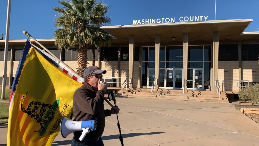 """A photo of a protester in St. George carrying a flag that says """"Don't tread on me."""""""