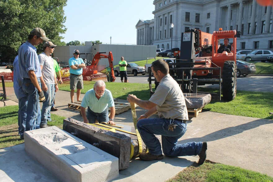 Workers prepare to use equipment to lift broken pieces of the Ten Commandments monument from the ground Wednesday morning after the driver of a vehicle intentionally crashed into it, authorities say.
