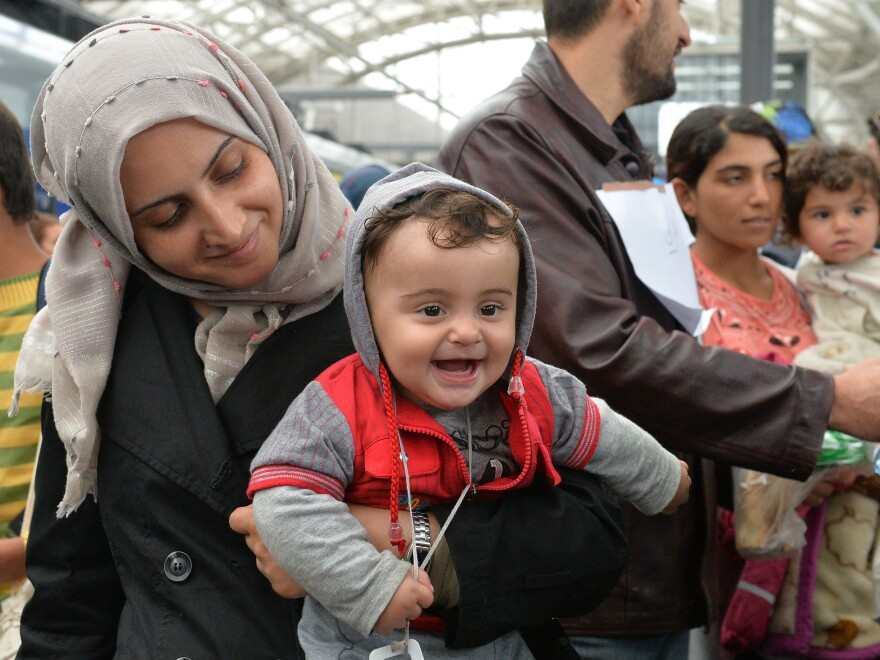 A woman holds her smiling baby in her arms as she arrives at the Hauptbahnhof station in Salzburg, Austria, on Saturday on their way with other migrants from Hungary via Vienna to Germany.