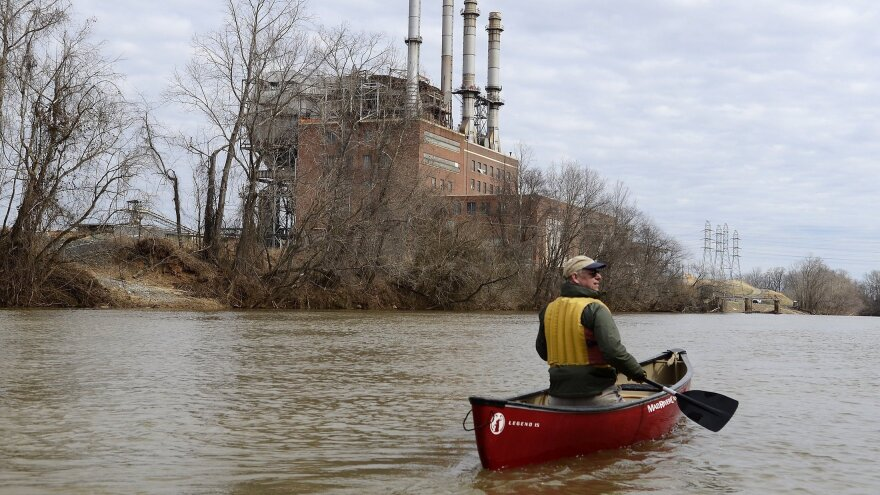 Mark Bishopric, a managing partner of Three Rivers Outfitters, paddles past the Duke Energy Dan River Steam Station in February 2014. Tens of thousands of tons of coal ash leaked into the river from a retaining pond below the steam station.