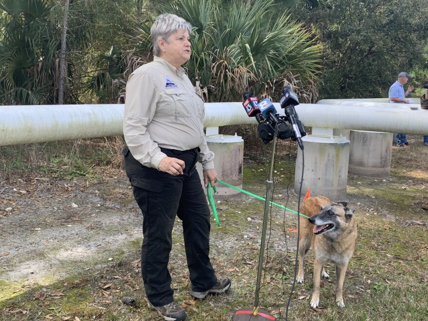 Woman with search dog stands, speaking into microphones.