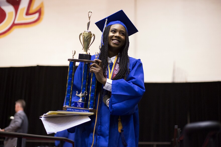 Ngone walks off the stage with her valedictorian trophy.