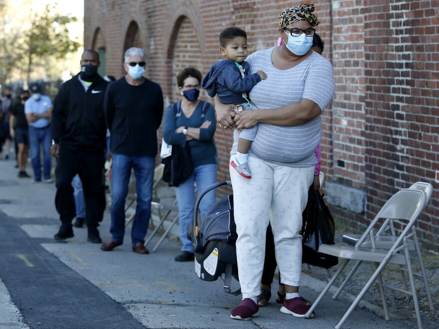 A woman holds her one year-old son as they wait in line to get a coronavirus test.
