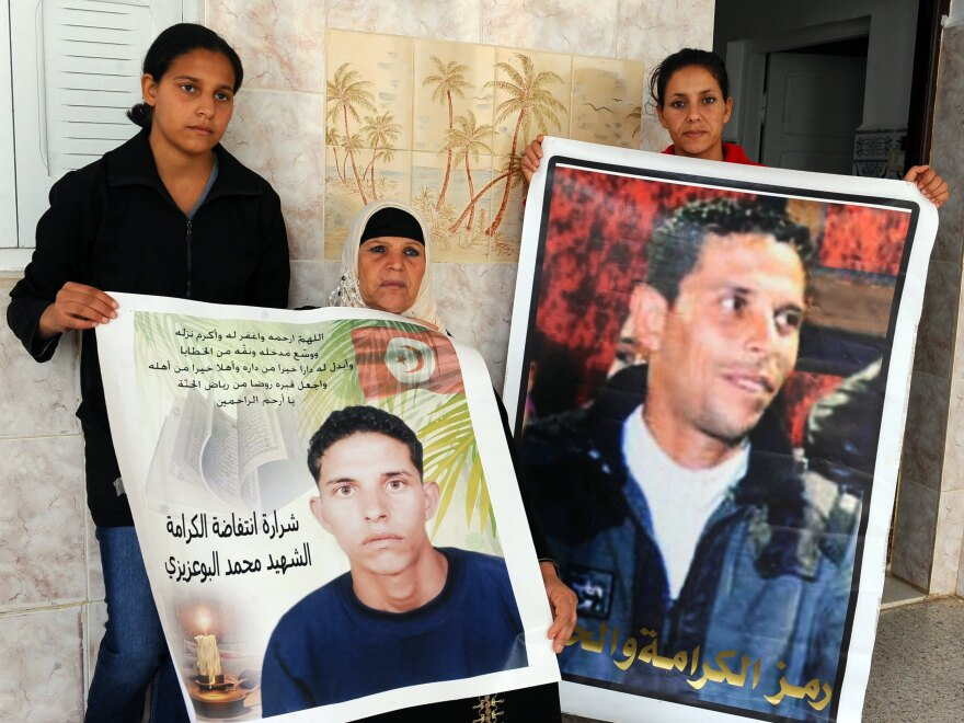 Manoubia Bouazizi (center) holds signs showing her son Mohamed along with her daughters, Basma (left) and Leila, in 2011. Mohamed's self-immolation in December 2010 was part of the impetus to the revolution that later ousted a dictator in Tunisia.