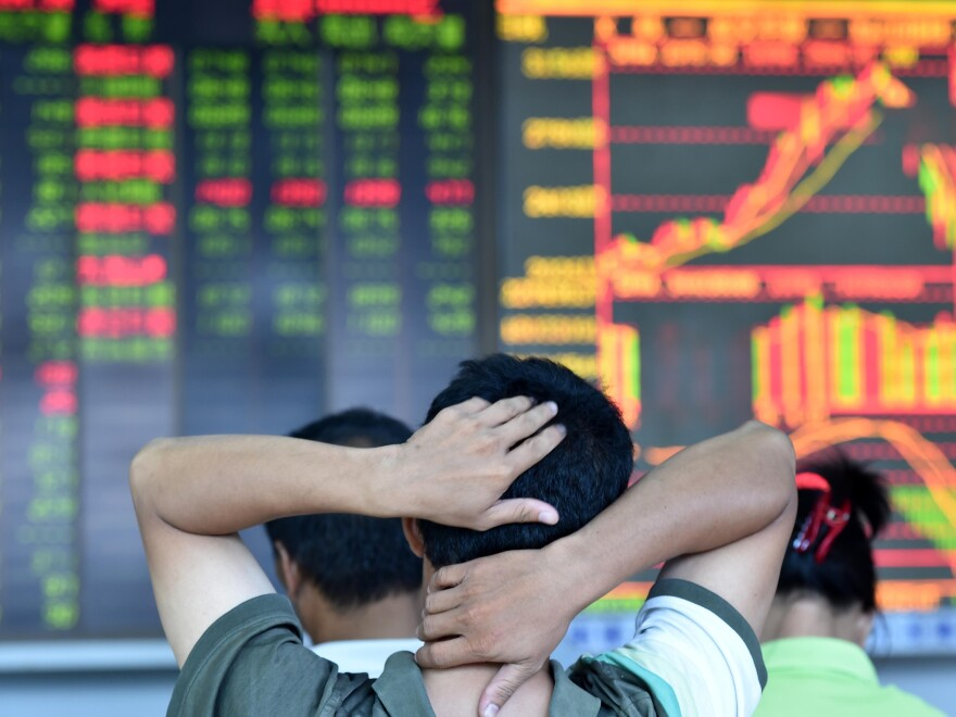 An investor looks through stock information at a trading hall in Haikou, the capital of Hainan province in southern China. Since mid-June, the main Shanghai stock index has lost 30 percent.