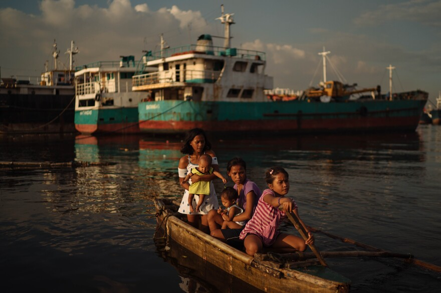 Sisters Joan (center) and Jossa Garcia (left), both teen mothers, hang out in a boat with their children and their younger sister. Joan dropped out of school after becoming pregnant at 14.