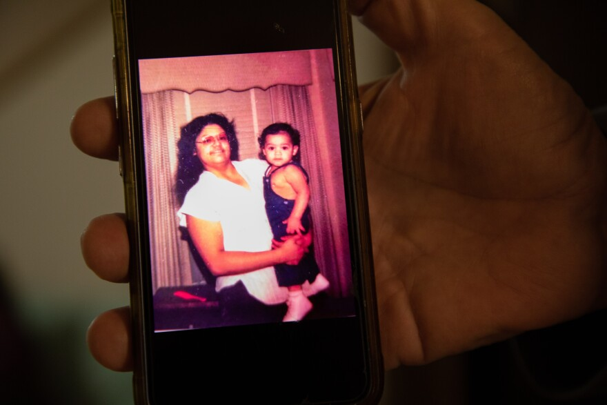 In an old photo, Arlene Ponce smiles at the camera while she holds her infant son Jojo.